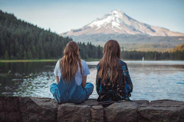 sisters sitting by lake